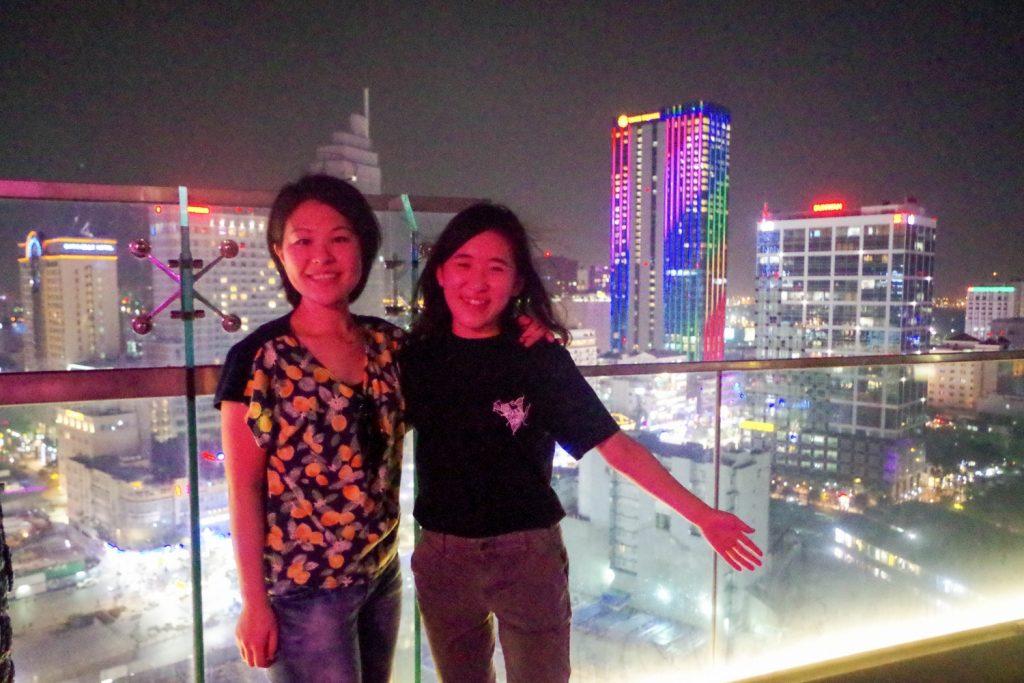 ホーチミンの夜景の前で写真を撮る佐田さん